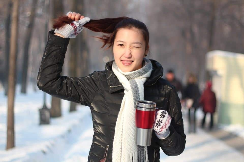 young girl walking with coffee in her hand in winters